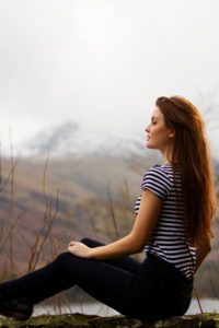 Girl sitting on wall with mountain background. Blue and white striped top.
