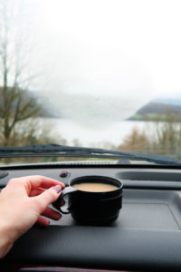 Flask coffe cup on dashboard of car. Lake in background.