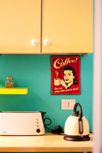 Red retro coffe poster on wall in retro style hotel in Rome Italy. White toaster and kettle.