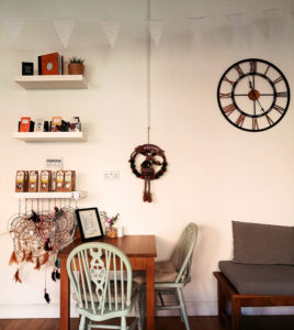 Metal clock on white wall. Grey chairs at wood table.