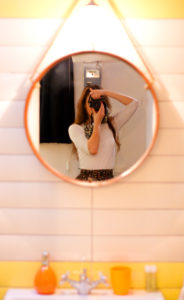 Girl's reflection in round mirror. Selfie girl.