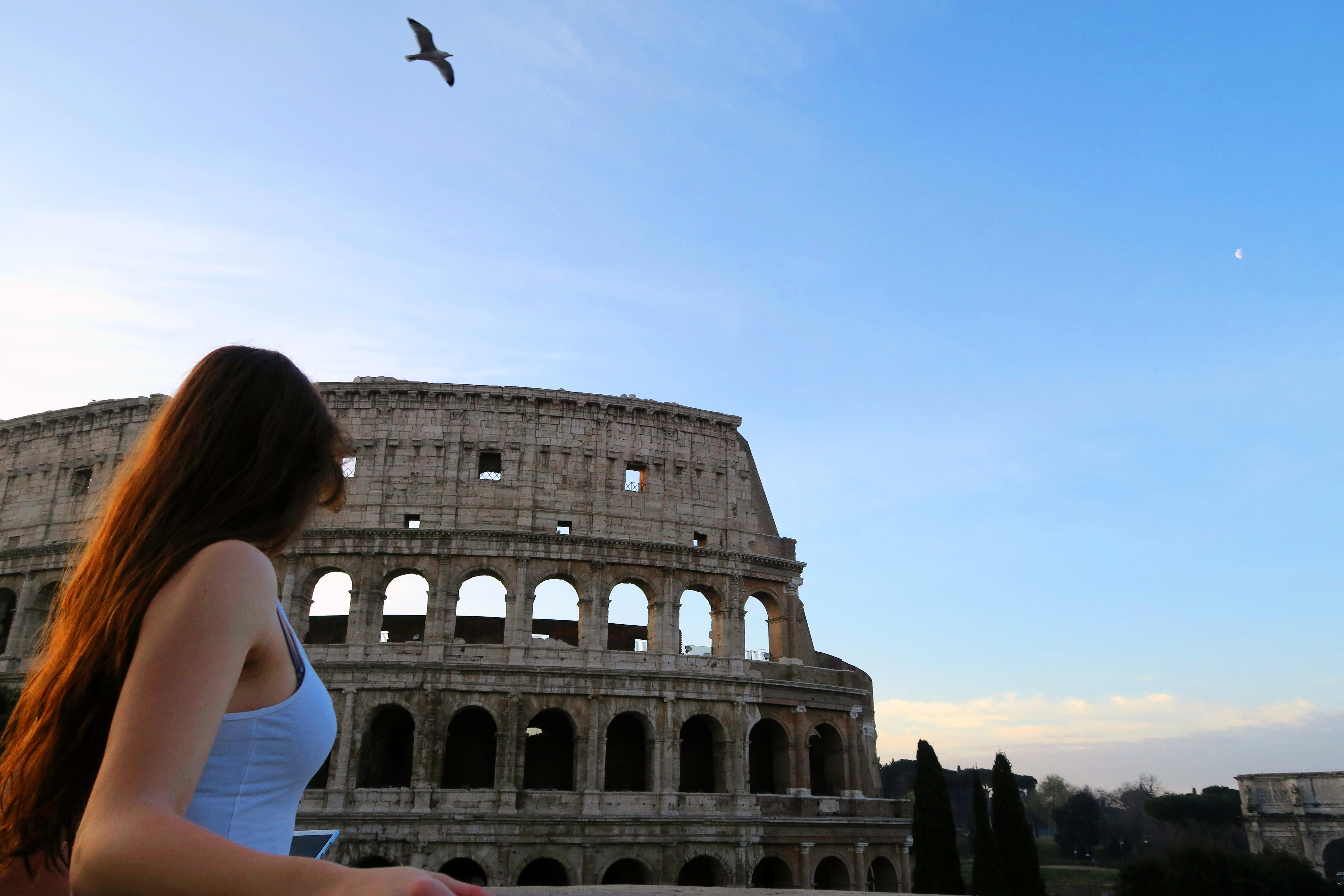 Girl standing in fron of Colosseum Rome Italy at sunrise. Blue sky.