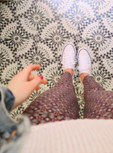Girl looking down on circle pattern ceramic tile flooring. Retro style hotel in Rome Italy. Converse style shoes.