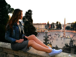 Girl tourist sat on wall in Rome Italy