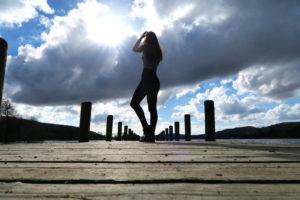 Girl stood on wooden jetty. Blue sky background.