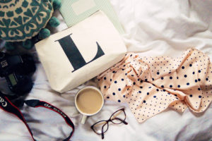 White monogram make-up bag and pink spotted scarf