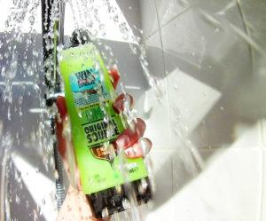 Green shower gel bottle under stream of water