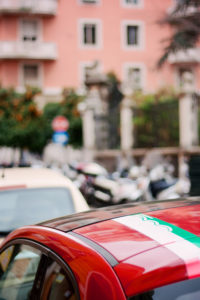 Green and white stripe on Red Fiat 500 car. Rome Italy.