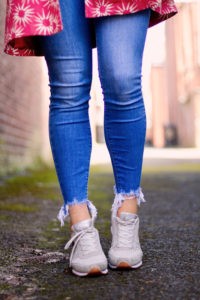 Blue chewed ankly cropped jeans and pale grey trainers.