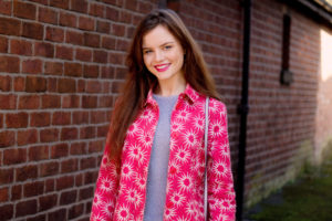 Girl wearing read Boden coat with white starburst pattern. Brick wall background.