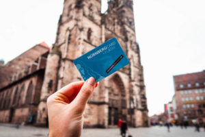 Female hand holding Nurnbergcard in front of old building