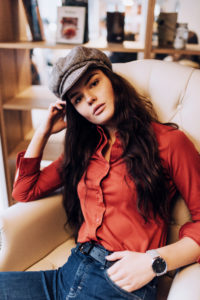 Young woman wearing 70s style outfit lounging in leather chair