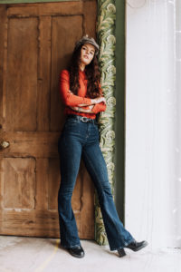 Female model wearing 70s style outfit with flared jeans