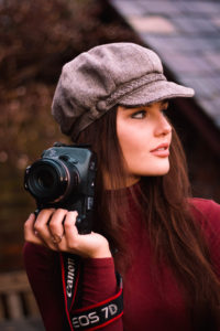 Female model wearing baker boy hat and holding Canon 7d DSLR camera