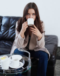 Young brunette model drinking mug of coffee