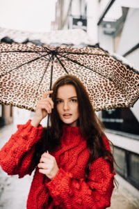 Young woman stood under leopard-print umbrella in Northern Quarter Manchester