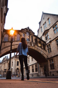 Girl walking towards Bridge of Sighs Oxford early morning