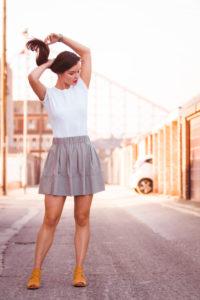 Young women wearing grey short skirt and white shirt