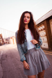 Young woman wearing denim jacket and grey short skirt