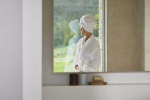 Reflection of girl wearing bathrobe in window