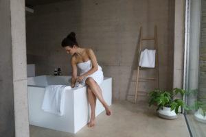 Woman wearing white Christy towel sat on side of bath
