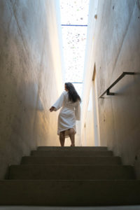 Woman wearing Christy bathrobe walking upstairs