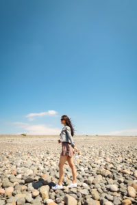 Girl walking on stoney beach Walney Island Cumbria