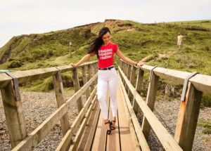 Young woman walking over bridge on beach in St Bees Cumbria