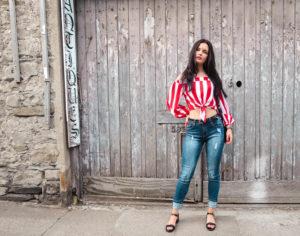 Female model stood in front of barn door wearing stripey top
