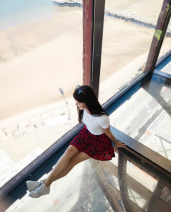 Girl sat on glass floor at top of Blackpool tower