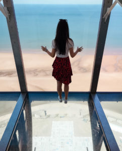 Girl stood on glass floor at top of Blackpool Tower