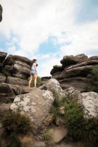 Young woman climbing at Brimham rocks Yorkshire