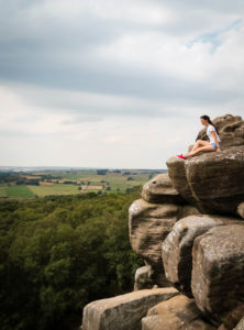 Young woman sitting on rock formation in Brimham Rocks Yorkshire
