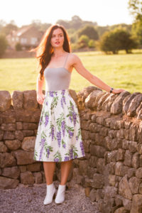 Girl leaning against dry stone wall in summer