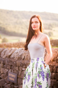 Young female brunette model in front of hills in summer