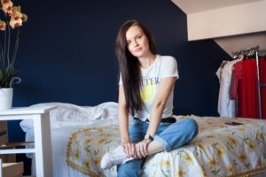 Young woman sat on bed in front of navy wall